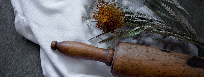 Antique rolling pin, dried flower and tea towel