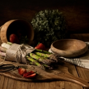 asparagus wrapped in paper with wooden bowl andcutting board