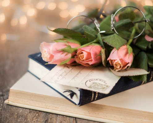 stack of books with pink roses and eye glasses and twinkle lights