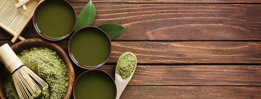 matcha green tea and matcha powder with bamboo and wooden spoons